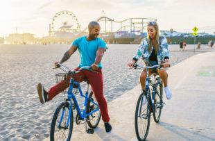 couple having fun riding bikes together at santa monica california near sunset